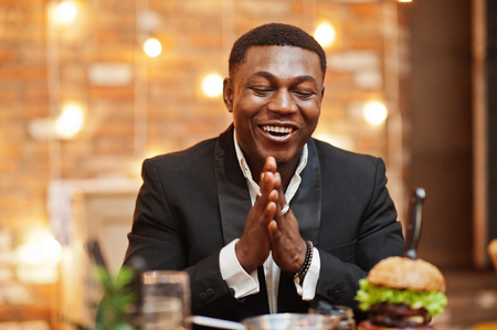 Hungry and happy rubs hands. Respectable young african american man in black suit sitting in restaurant with tasty double burger and soda drink.