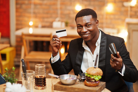 Respectable young african american man in black suit sitting in restaurant hold credit card and wallet with tasty double burger and soda drink.