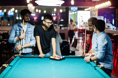Group of stylish asian friends wear on jeans playing pool billiard on bar. 免版税图像