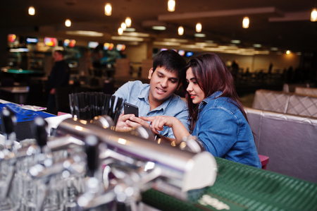 Stylish asian couple wear on jeans sitting on chair at bar in club and look on phone.