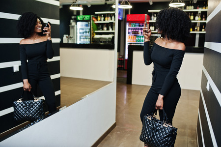 Fashionable young beautiful african american woman with afro hairstyle and handbag posing wear in elegant black.