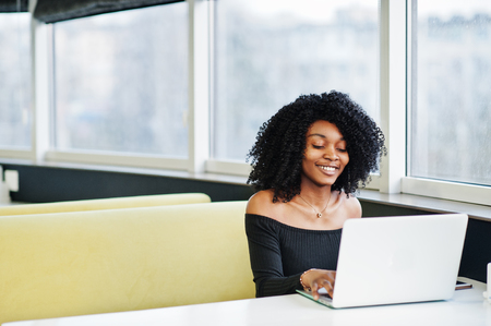 Fashionable young beautiful african american business woman with afro hairstyle wear in elegant black, sitting and working at laptop.