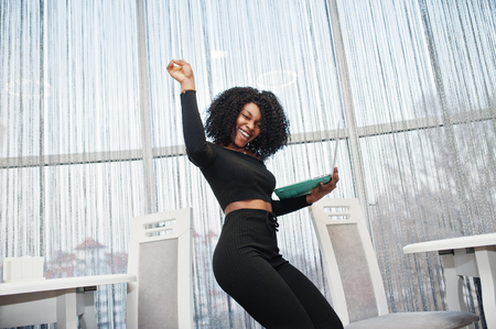 Happy and exults winner fashionable young beautiful african american business woman with afro hairstyle wear in elegant black, stand with laptop at hands. 스톡 콘텐츠