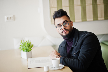 Arab man wear on black jeans jacket and eyeglasses sitting in cafe, read book and drink coffee.