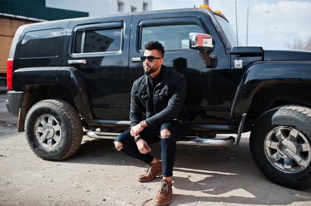 Fashion rich beard Arab man wear on black jeans jacket and sunglasses posed against big black suv car.