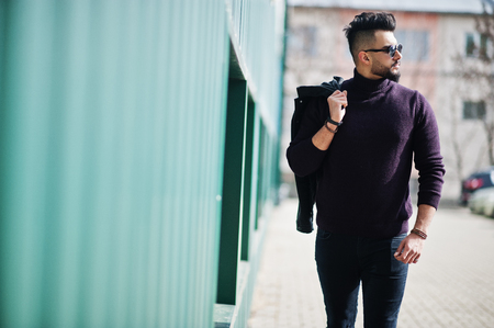 Fashion rich beard Arab man wear on turtle neck and sunglasses walking against green wall with jacket on hand.
