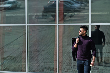 Fashion rich beard Arab man wear on turtle neck and sunglasses posed against large windows of modern building with jacket on hand. Stock Photo
