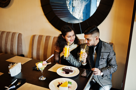 Lovely indian couple in love, wear at saree and elegant suit, sitting on restaurant and  drinks orange fresh juice from the tubule.