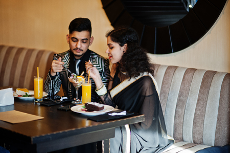 Lovely indian couple in love, wear at saree and elegant suit, sitting on restaurant and  eating ice cream together.