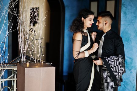 Lovely indian couple in love, wear at saree and elegant suit, posed on restaurant. Imagens - 119277088