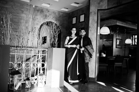 Lovely indian couple in love, wear at saree and elegant suit, posed on restaurant.