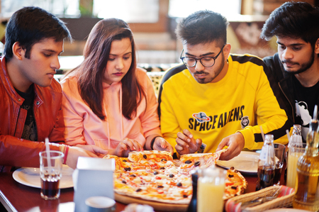 Group of asian friends eating pizza during party at pizzeria. Happy indian people having fun together, eating italian food and sitting on couch. Imagens