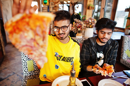 Asian friends guys eating pizza during party at pizzeria. Happy indian people having fun together, eating italian food and sitting on couch.