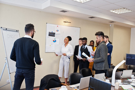 Mixed race business coach presenting report standing near whiteboard pointing on sales statistic shown on diagram and chart teach diverse company members gathered together in conference room.
