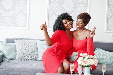 Two fashion african american models in red beauty dress, womans posing evening gown sitting on couch and having fun together.