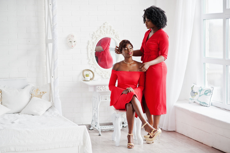 Two fashion african american models in red beauty dress, sexy womans posing evening gown at white vintage room.