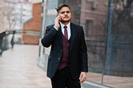 Elegante empresario indio en ropa formal de pie contra las ventanas en el centro de negocios y hablando por teléfono.
