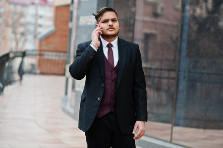 Stilvoller indischer Geschäftsmann in formeller Kleidung, der gegen Fenster im Business Center steht und am Telefon spricht.
