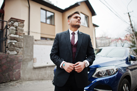 Rich indian businessman in formal wear standing against business suv car and his large mansion house.