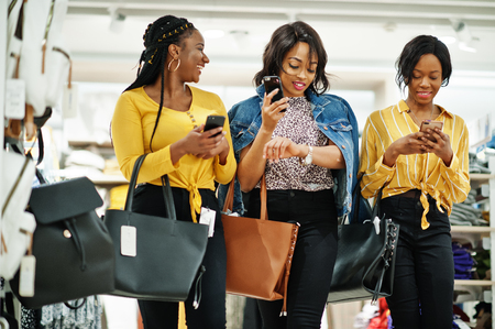 Three african woman at clothes store with new handbags. Shopping day. They look at mobile phones. Stock Photo