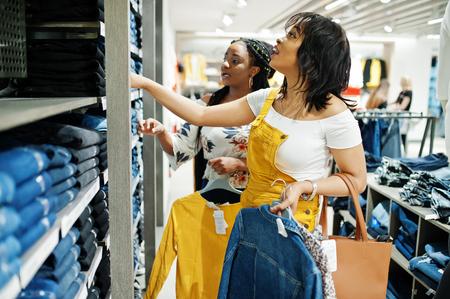 Three african woman choosing clothes at store. Shopping day. They buying jeans.