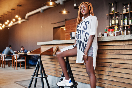 Beautiful african woman in stylish casual clothes posing near bar counter. Stock Photo