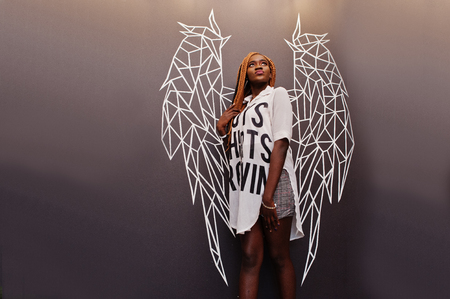 Beautiful african woman in stylish casual clothes posing against angel wings wall. Stock fotó