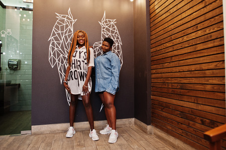 Two african womans in stylish casual clothes posing against angel wings wall.