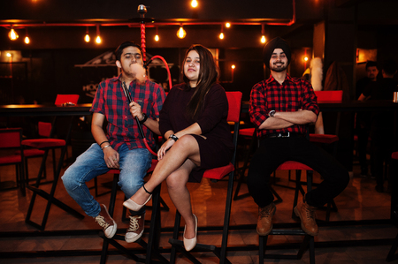 Group of indian friends sitting at lounge bar, smoke hookah and having rest.