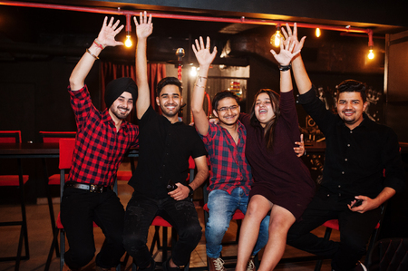 Group of indian friends sitting at lounge bar, having fun and rest. Hands up. Stockfoto