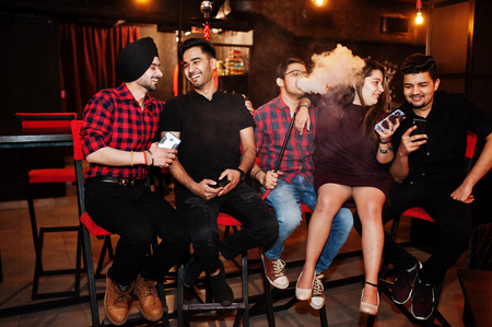 Group of indian friends sitting at lounge bar, having fun and rest, smoking hookah and looking on mobile phones.