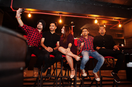 Group of indian friends sitting at lounge bar, having fun and rest, smoking hookah and looking on mobile phones to make selfie. Imagens