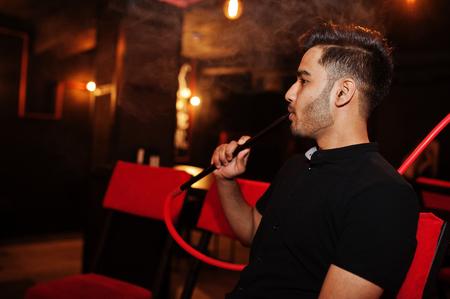 Asian man smoke hookah and having rest at lounge bar.