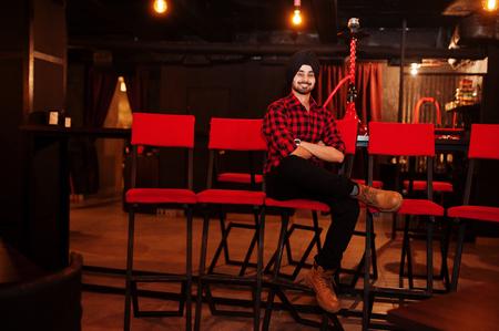 Indian man in checkered shirt and black turban sitting at bar.