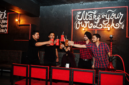Make your own luck! Group of indian friends having fun and rest at night club, drinking cocktails, cheers and smoke hookah.