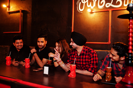 Group of indian friends having fun and rest at night club, drinking cocktails and smoke hookah.