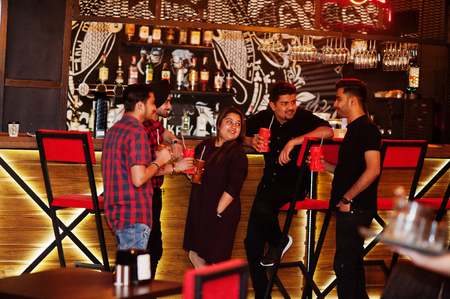 Group of indian friends having fun and rest at night club, drinking cocktails near bar counter. Imagens