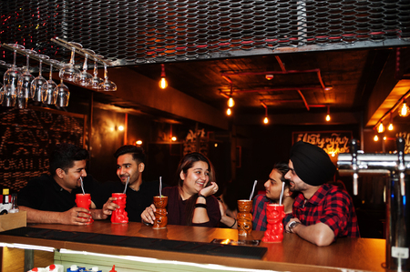 Group of indian friends having fun and rest at night club, drinking cocktails near bar counter.
