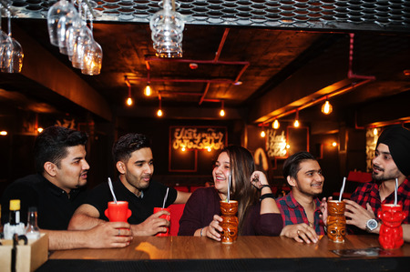Group of indian friends having fun and rest at night club, drinking cocktails near bar counter. Stockfoto