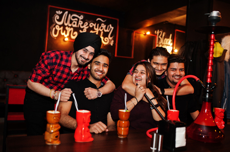 Group of indian friends having fun and rest at night club, drinking cocktails and smoke hookah. Imagens