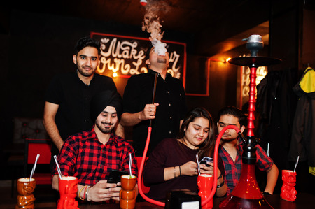 Group of indian friends having fun and rest at night club, drinking cocktails and smoke hookah, looking at mobile phones.