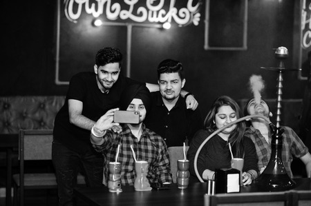 Group of indian friends having fun and rest at night club, drinking cocktails and smoke hookah, looking at mobile phones and making selfie. Imagens