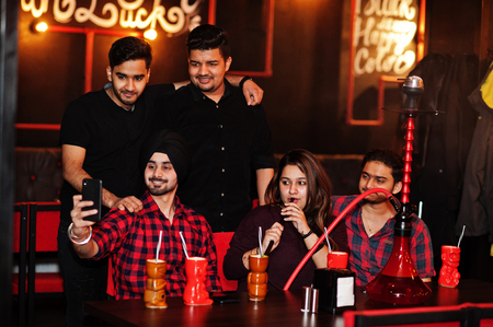 Group of indian friends having fun and rest at night club, drinking cocktails and smoke hookah, looking at mobile phones and making selfie.