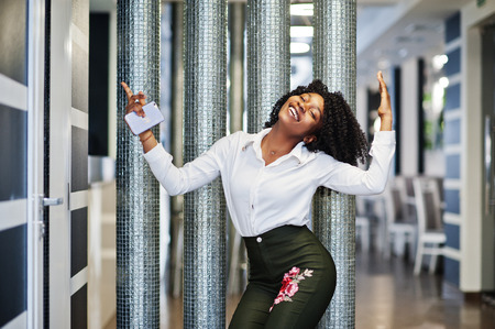 Yes yes yes! Ð¡heerful business african american lady with afro hair, wear white blouse and green pants dancing in cafe.