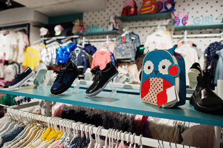 Children's bright clothes hang on the display in the baby clothing store. Girls section. Shoes with backpack. 免版税图像