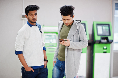 Two asian guys looking at mobile phone against row of green ATM.