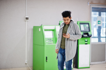 Young stylish asian man with mobile phone against row of green ATM.