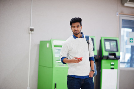 Young stylish asian man with mobile phone and backpack against row of green ATM.