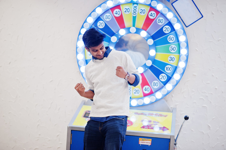 I'm a millionaire! Very excited young asian man against fortune wheel win at lottery great prize. Banco de Imagens