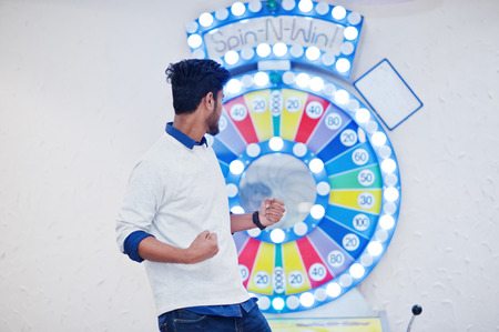 Im a millionaire! Very excited young asian man against fortune wheel win at lottery great prize. Stok Fotoğraf